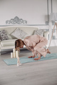Young lady doing gymnastics on floor at home - PhotoDune Item for Sale