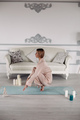 attractive blonde woman meditating on the yoga mat near the grey sofa - PhotoDune Item for Sale