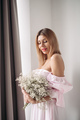 Pretty smiling young woman standing with a bouquet of flowers - PhotoDune Item for Sale