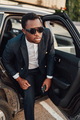 African businessperson with sunglasses getting out of car - PhotoDune Item for Sale
