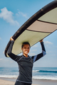 Cheerful woman in wetsuit holding surfboard on beach - PhotoDune Item for Sale