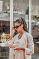 Tanned woman with coffee wearing sunglasses outdoors - PhotoDune Item for Sale