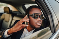 Successful african businessman with phone inside of car - PhotoDune Item for Sale