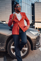 Cheerful african businessperson with phone and car outside - PhotoDune Item for Sale