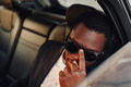 Fashionable african employee with sunglasses inside of car - PhotoDune Item for Sale