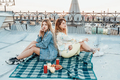 Two girlfriends sitting on rooftop side by side - PhotoDune Item for Sale