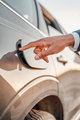 Shot of human hand opening fuel tank of car - PhotoDune Item for Sale