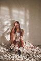 Tanned woman with dreadlocks sitting around wall - PhotoDune Item for Sale