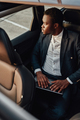 Serious black employee working on laptop inside of car - PhotoDune Item for Sale
