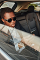 Cool african businessperson with phone sitting inside of car - PhotoDune Item for Sale