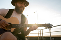 Young bearded man playing guitar on rooftop patio - PhotoDune Item for Sale