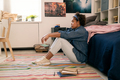 Tired or upset teenage girl sitting on the floor by her bed - PhotoDune Item for Sale