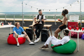 Group of restful friends with drinks listening to bearded man playing guitar - PhotoDune Item for Sale