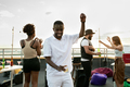 Happy young African man dancing at rooftop party - PhotoDune Item for Sale