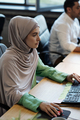 Pretty Muslim businesswoman sitting in front of computer - PhotoDune Item for Sale
