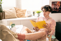 Restful teenager reading book with his legs on desk - PhotoDune Item for Sale