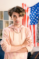 Youthful guy with his arms crossed by chest standing against US flag - PhotoDune Item for Sale