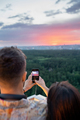 Young man and woman photograpging cloudy sky at sunset - PhotoDune Item for Sale