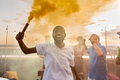 Young ecstatic African man with yellow smoke cracker - PhotoDune Item for Sale