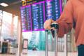 Young asian woman standing at the airport holding suitcase checking departure - PhotoDune Item for Sale