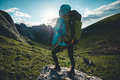 Successful woman backpacker hiking on sunset alpine mountain top - PhotoDune Item for Sale