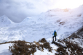 Successful woman backpacker hiking in winter mountains - PhotoDune Item for Sale