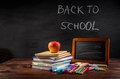 Pile of book and exercise books with school applies and apple snack with chalkboard - PhotoDune Item for Sale