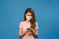 Young Asia girl wearing medical face mask using mobile phone on blue background. - PhotoDune Item for Sale