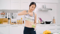 Sporty Asian woman drinking apple juice in the kitchen. - PhotoDune Item for Sale