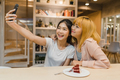 Cheerful young Asia friend clicking selfie using mobile phone at a coffee shop. - PhotoDune Item for Sale