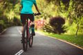 Woman cycling on tropical park trail in summer - PhotoDune Item for Sale
