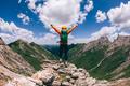 Successful woman backpacker hiking on alpine mountain peak - PhotoDune Item for Sale