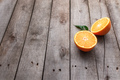 Fresh orange fruit halves or cuts with green leaf on old wooden background table - PhotoDune Item for Sale
