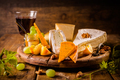Cheese platter, assortment of different cheeses with glass of red wine on wooden table - PhotoDune Item for Sale