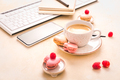 Feminine business workplace with keyboard, writing supplies, cup of coffee and small macarons - PhotoDune Item for Sale