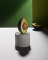 Creative avocado balance on the concrete stand, green background - PhotoDune Item for Sale