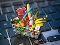 Grocery food buying online and delivery concept. Shopping basket full of food on laptop keyboard. - PhotoDune Item for Sale
