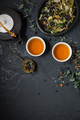 Herbal tea with teapot and herbal leaves on black stone background - PhotoDune Item for Sale