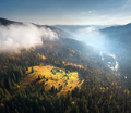 Aerial view of beautiful village in mountains in low clouds - PhotoDune Item for Sale