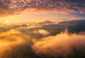 Mountains in low clouds at sunrise in summer. Aerial view - PhotoDune Item for Sale