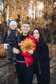 Caucasian family in autumn park.They are standing on the bridge against blurred yellow trees - PhotoDune Item for Sale