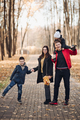 Caucasian family goes for a walk in the autumn park with two children - PhotoDune Item for Sale