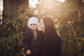 Loving mother kissing her daughter in autumnal forest - PhotoDune Item for Sale
