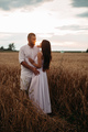 Beautiful couple standing in the field. field at sunset - PhotoDune Item for Sale