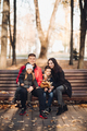 Smiling parents and kids sitting on the bench outdoors - PhotoDune Item for Sale