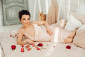 Beautiful sensual pregnant woman on bed with roses - PhotoDune Item for Sale