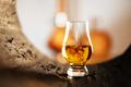 A glass of whiskey in oak barrel - PhotoDune Item for Sale