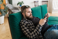 Young man surfing on social networking site using smartphone. Technologies and internet concept - PhotoDune Item for Sale