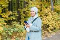Islamic young woman wearing hijab standing on autumn park background. Modern arabian muslim girl - PhotoDune Item for Sale