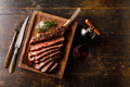 Grilled sliced Tomahawk Steak on bone and glass of Red wine on wooden background - PhotoDune Item for Sale